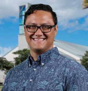 Portrait photo of Dr. Kamuela Yong. He is wearing a blue on blue aloha shirt. The background is the library building