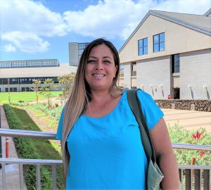 Photo of a woman in a blue blouse with UH West Oahu Campus behind her