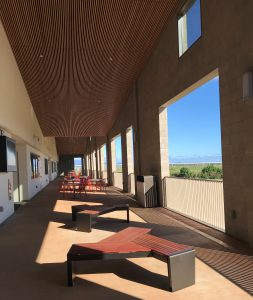 Photo of a broad lanai with openings letting lots of light in. There are seating areas in the middle and classrooms to the left