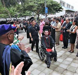 Photo of Jarek Barnett at his 2016 graduation. Faculty and administrators line a path. At the center of the photo is Barnett making his way down the gantlet in his wheelchair