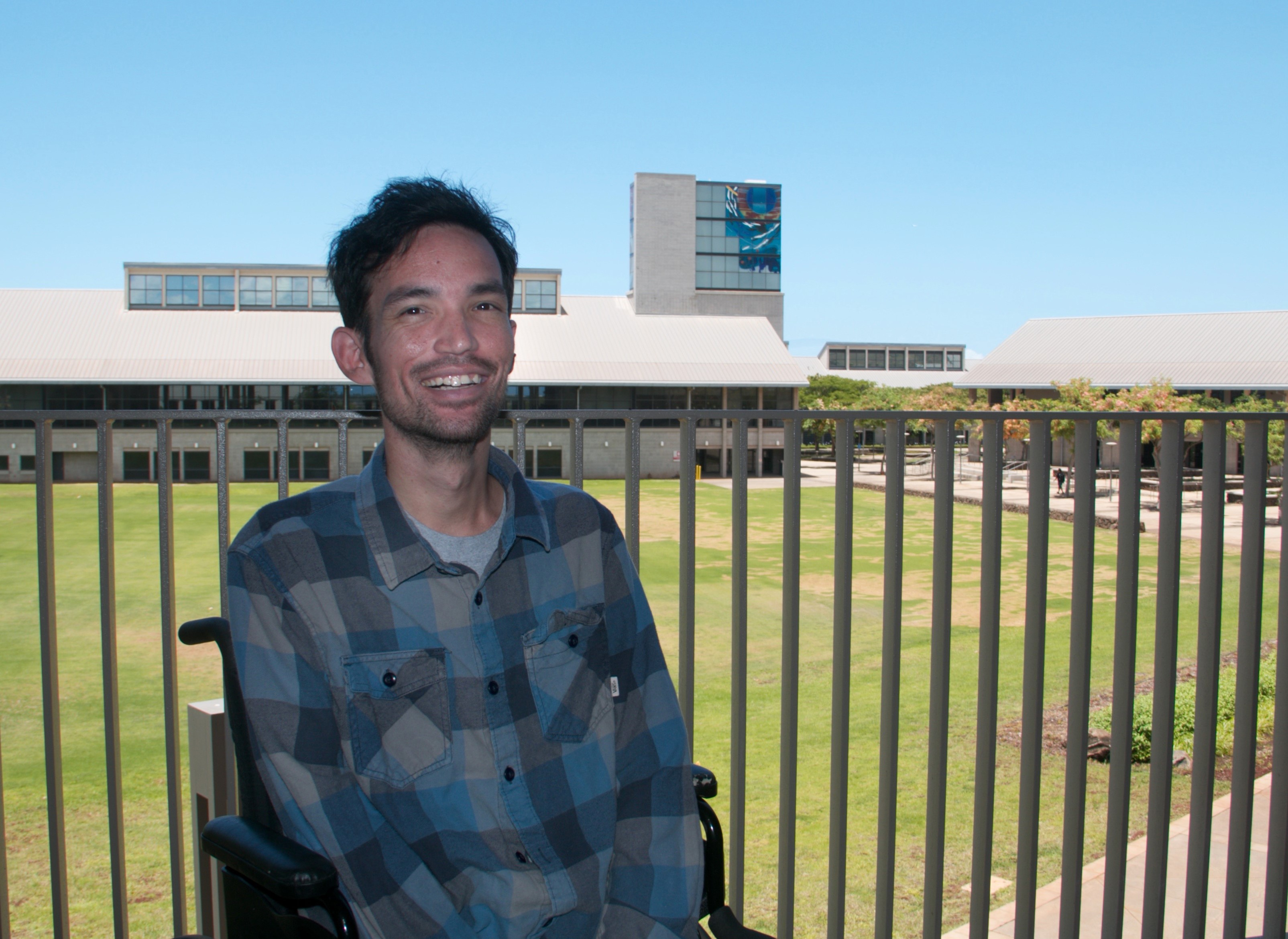 Photo of a man sitting in a wheelchair. Behind him is a metal railing and beyond that is the UH West Oahu campus - You can see portions of the Great Lawn, the Library, Campus Center and the Laboratory building