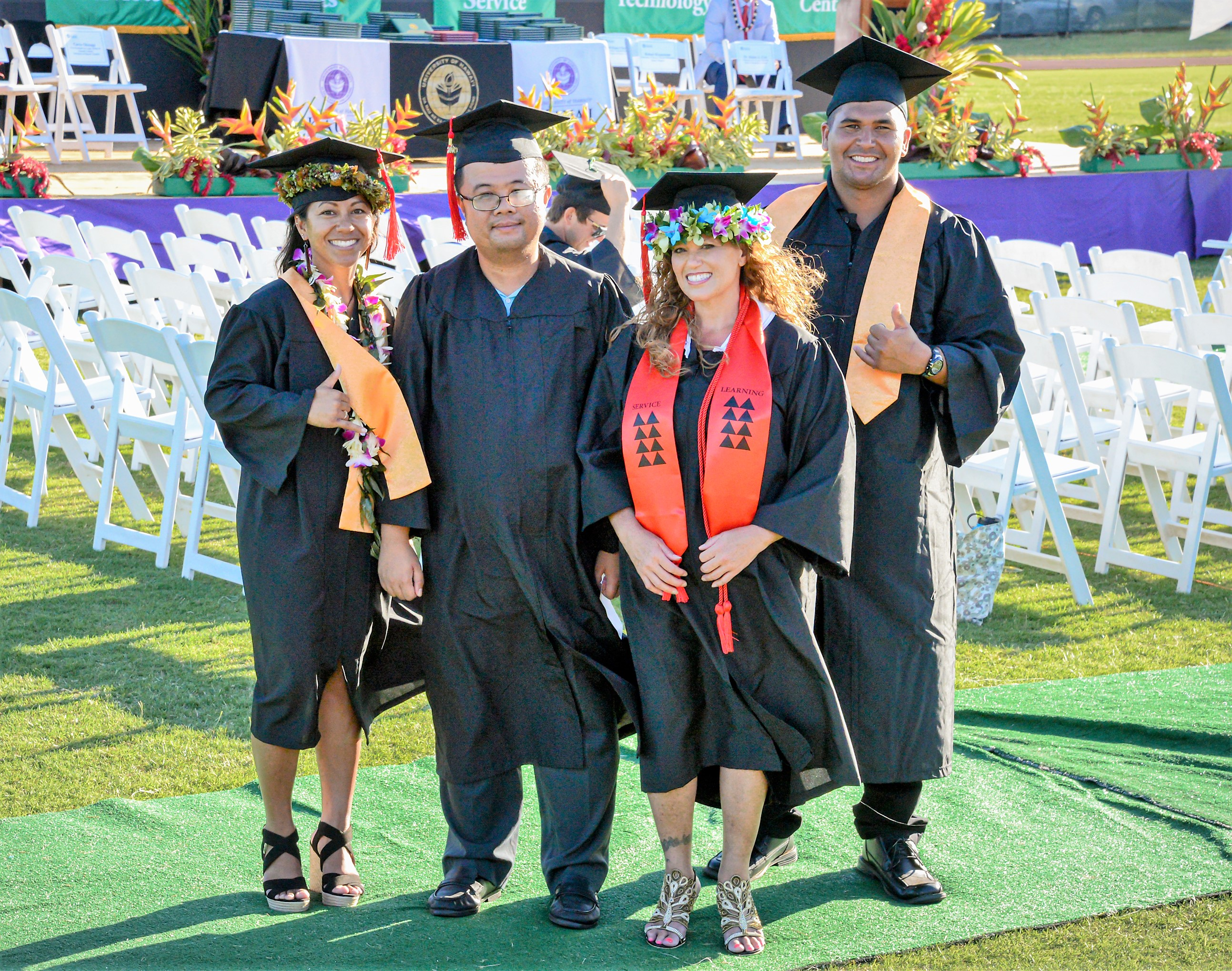 photo of four people in graduation caps and gowns standing on a grassy lawn with white folding chairs and a stage in the background. There are two men and two women. One of the men is flashing a shaka sign