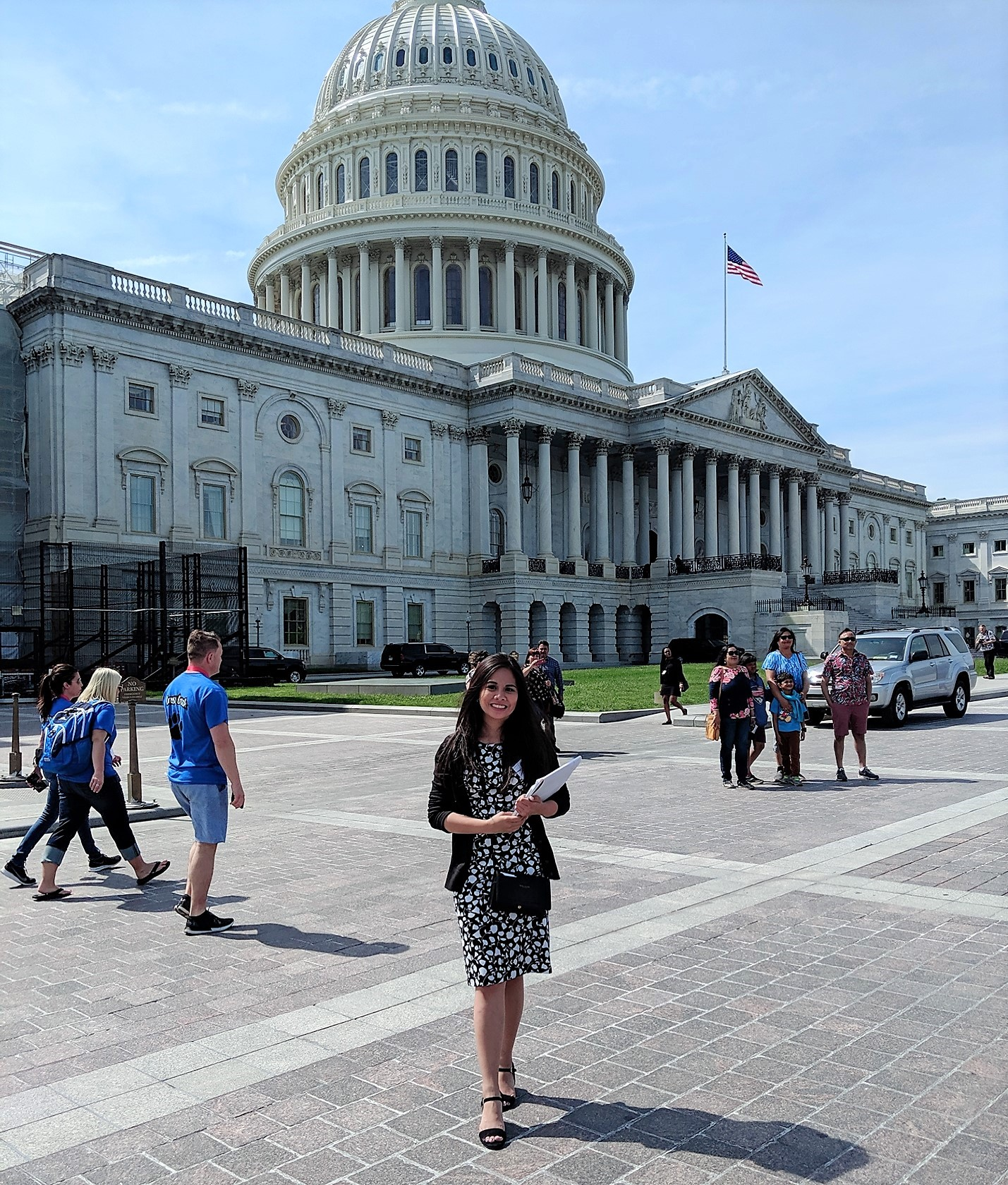 Photo of a woman holding some papers posed in front of the U.S. Capitol. It is a bright, sunny day and in the background tourists are walking around