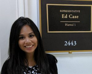photo of a woman standing next to a sign that says Representative Ed Case Hawaii. She is smiling as she looks into the camera
