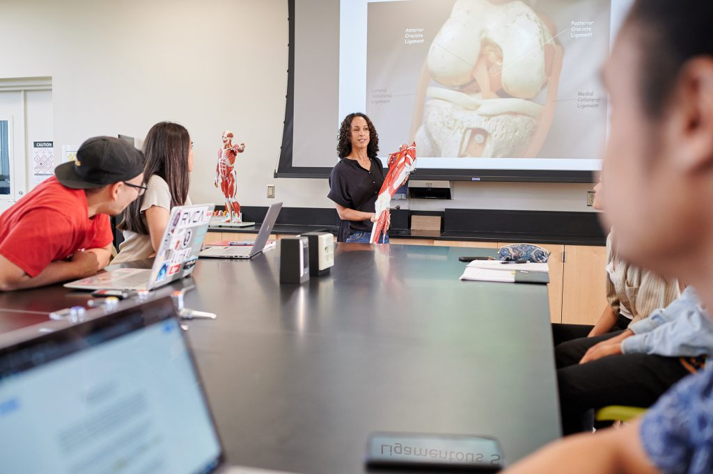 Photo of a professor in a classroom and students listening to her. The professor is holding what appears to be a model of the human leg and on the screen behind her is a diagram of a human leg