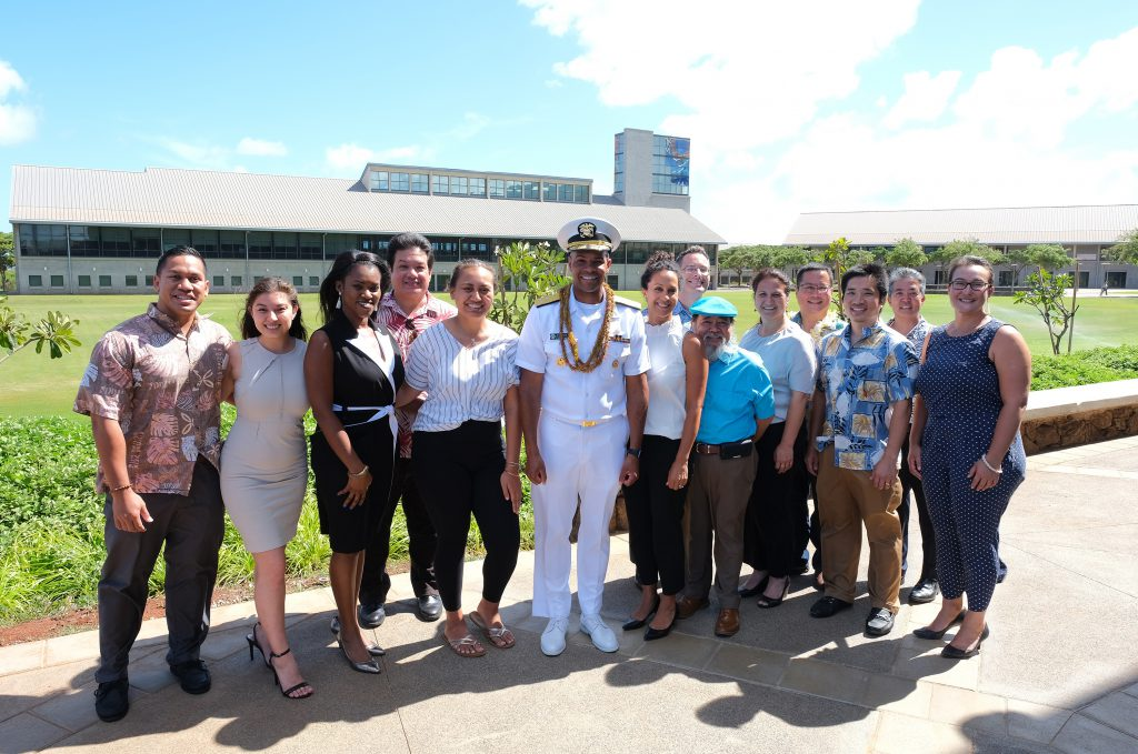 Photo of a group of people with a man in a white uniform standing at center. In the background is the UH West Oahu Great Lawn and the James & Abigail Campbell Library