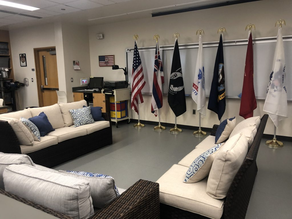 Pictures of couches where students can gather at the UH West O'ahu Veterans Lounge, decorated with flags representing the U.S. Armed Forces.