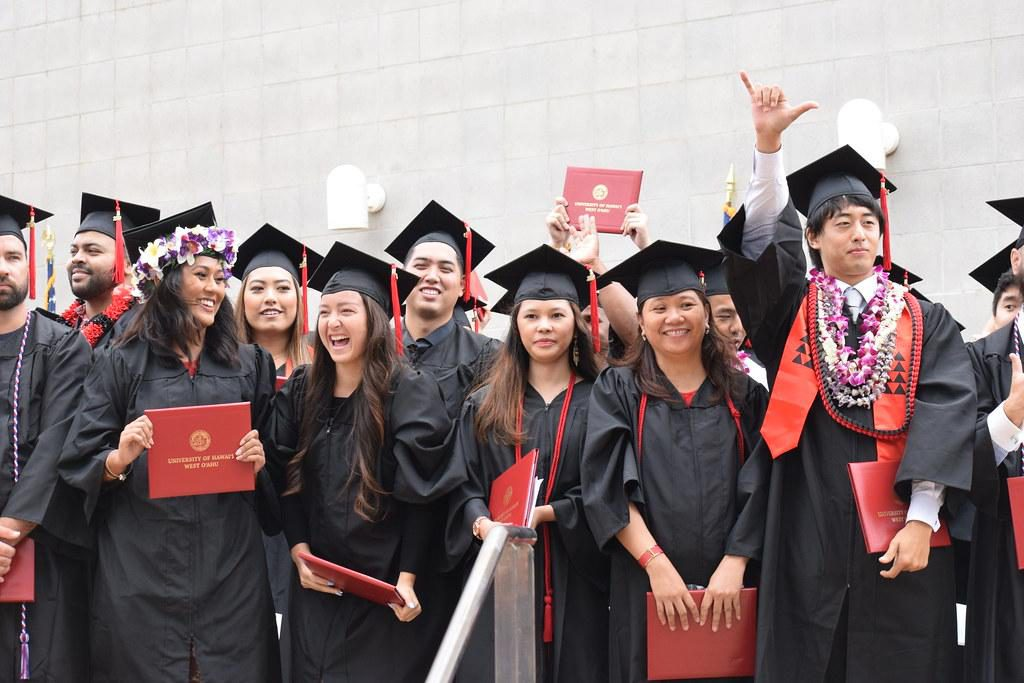 photo of graduates standing and celebrating during a commencement ceremony