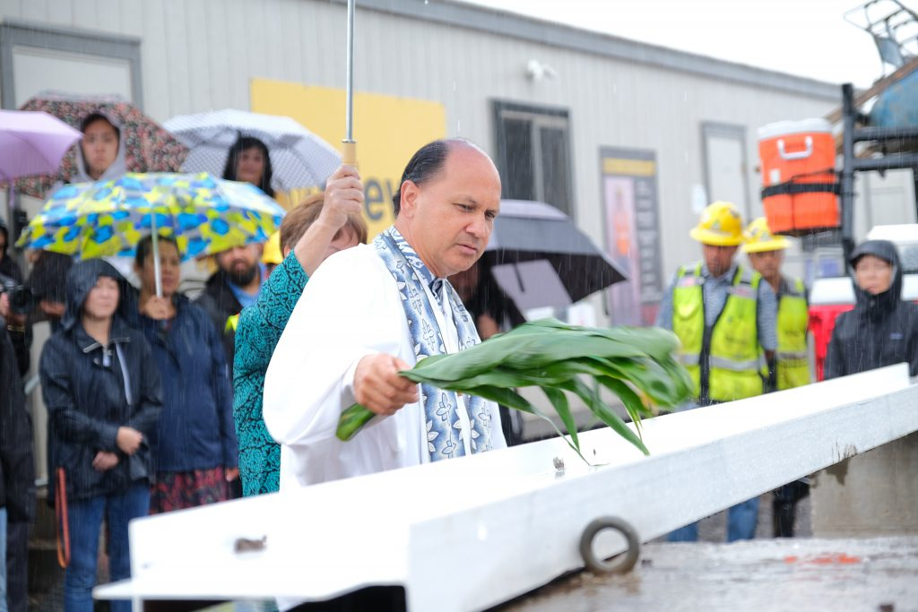 Kahu Kordell Kekoa blesses the beam by sprinkling water with a ti leaf.