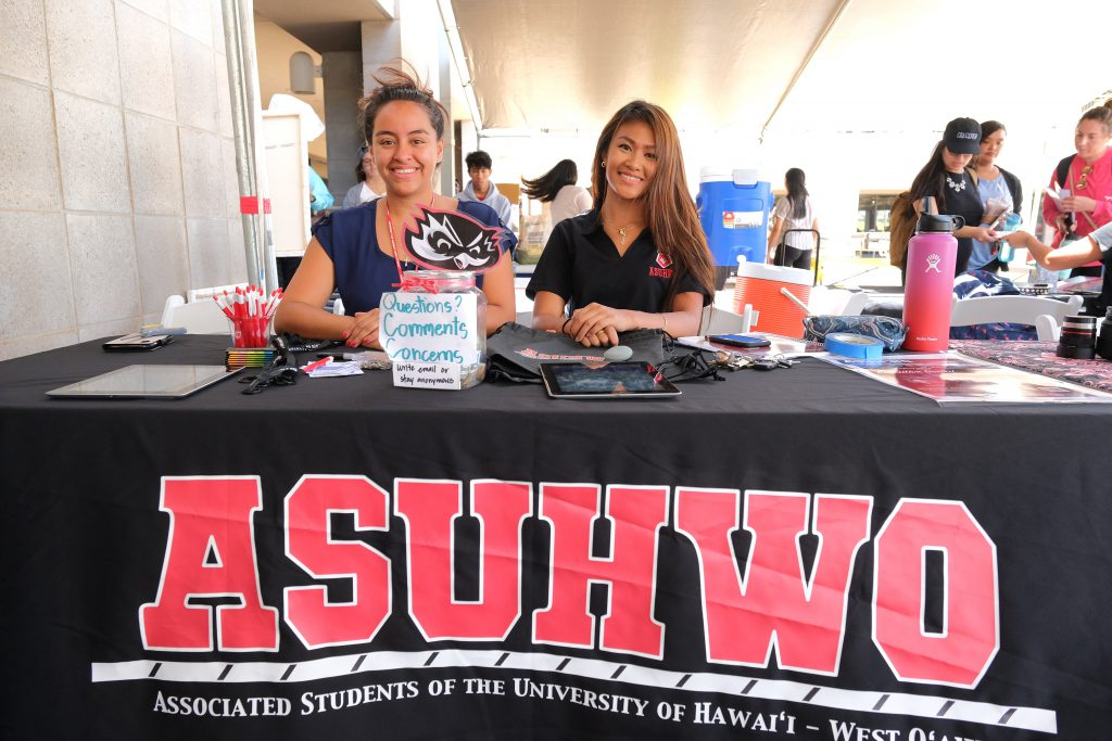 Two female students smiling, sitting at a table to promote the Associated Students of the University of Hawaii-West Oahu.