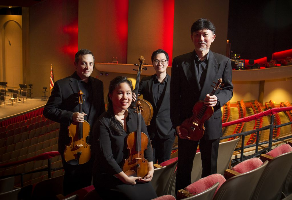 Members of the Chamber Music Hawaii's Galliard String Quartet posing in the audience seating with the stage behind them.
