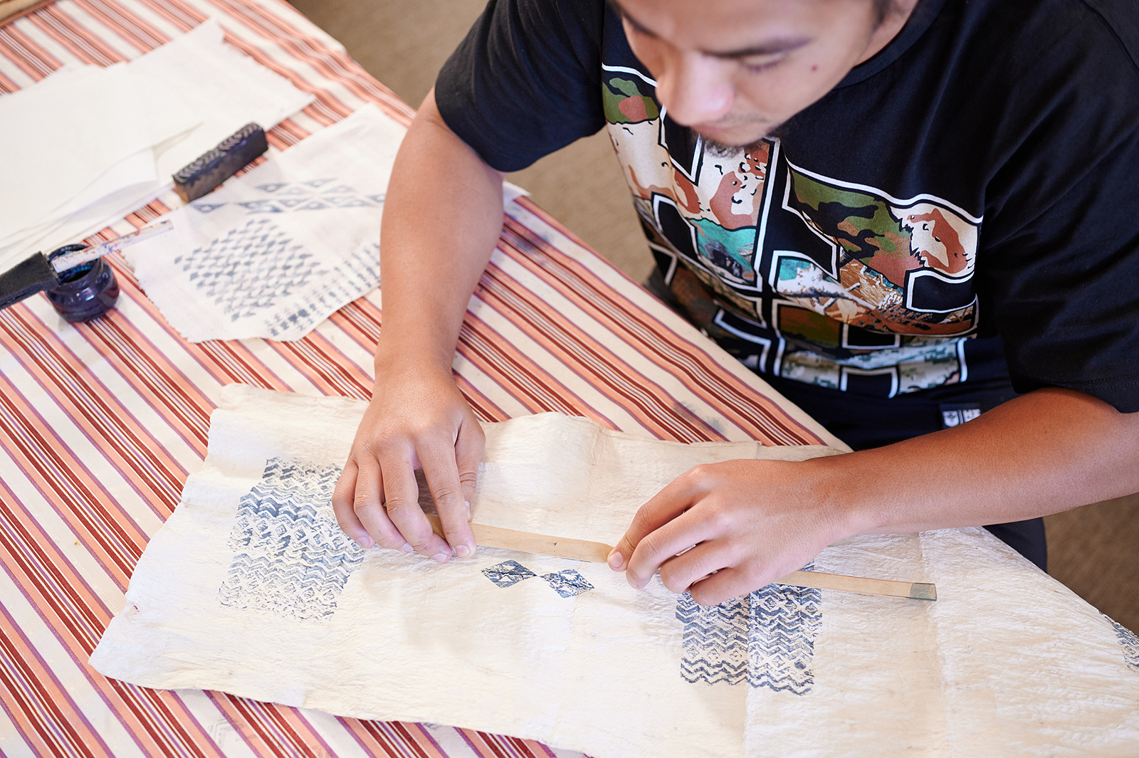 Person stamping geometric patterns on a cloth.