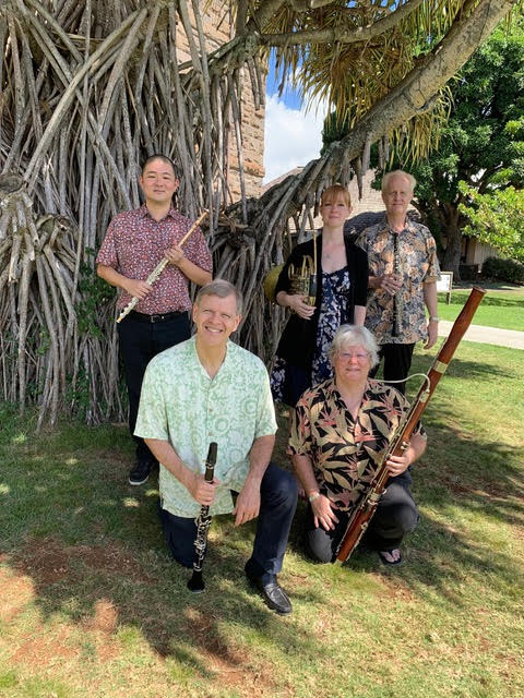 Members of Chamber Music Hawaiiʻs Spring Wind Quintet pose outdoors for a group photo while holding various instruments.