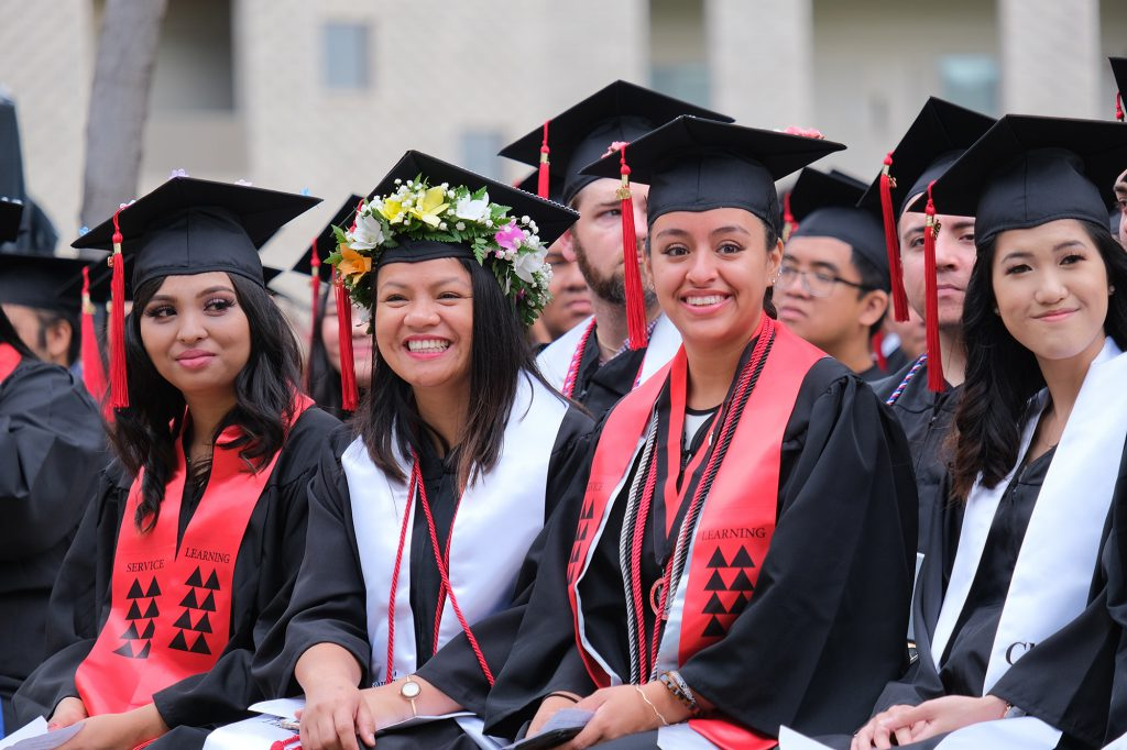 Graduates from the Fall 2019 class smiling at the commencement ceremony.