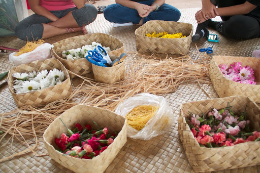 Various plant materials sorted in woven baskets, all on a woven mat on the floor.