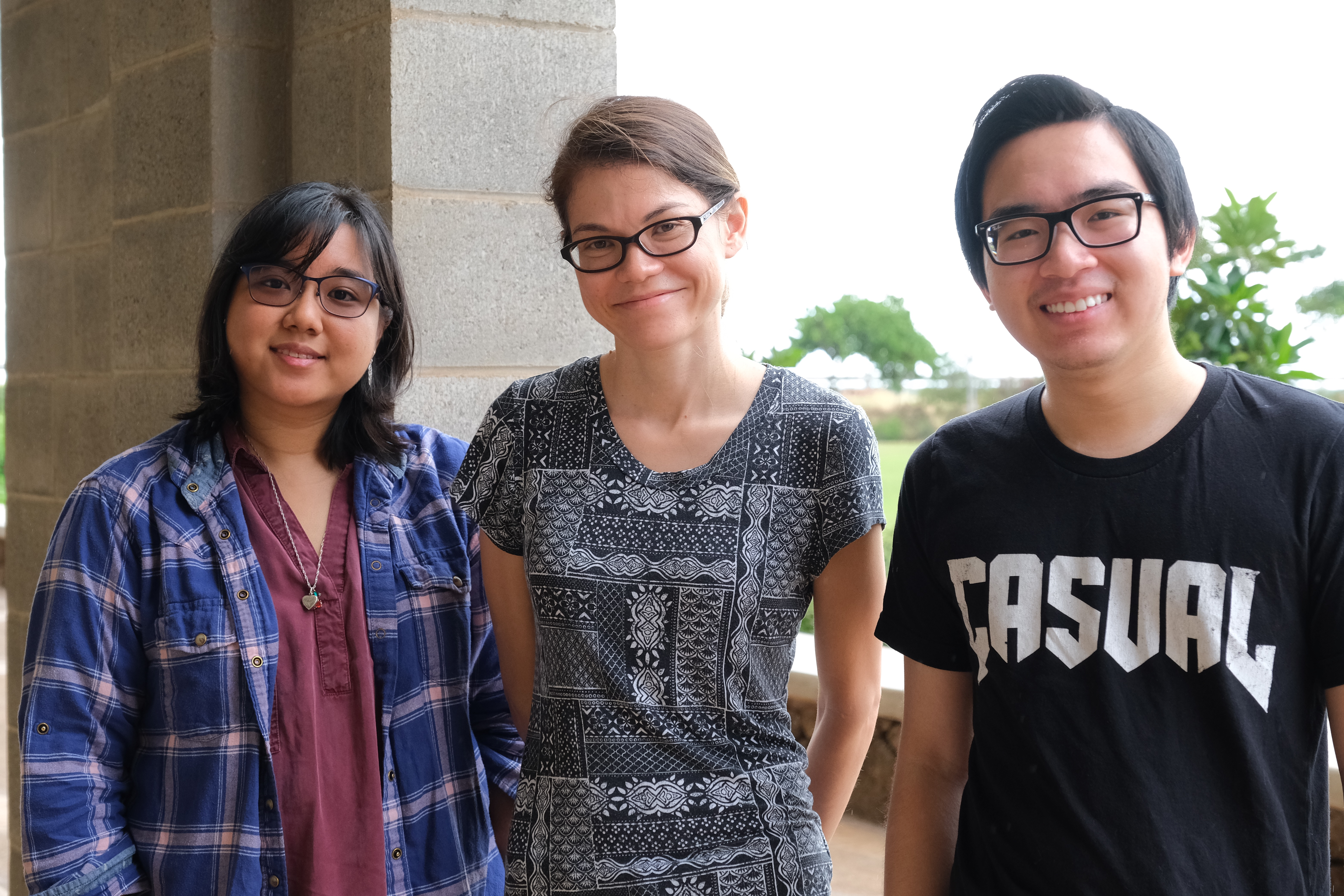 Outdoor group photo of a professor standing between two of her students.