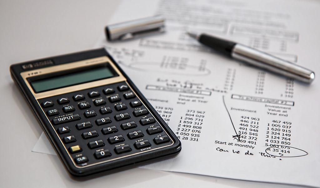 Black calculator near ballpoint pen on white printed paper.