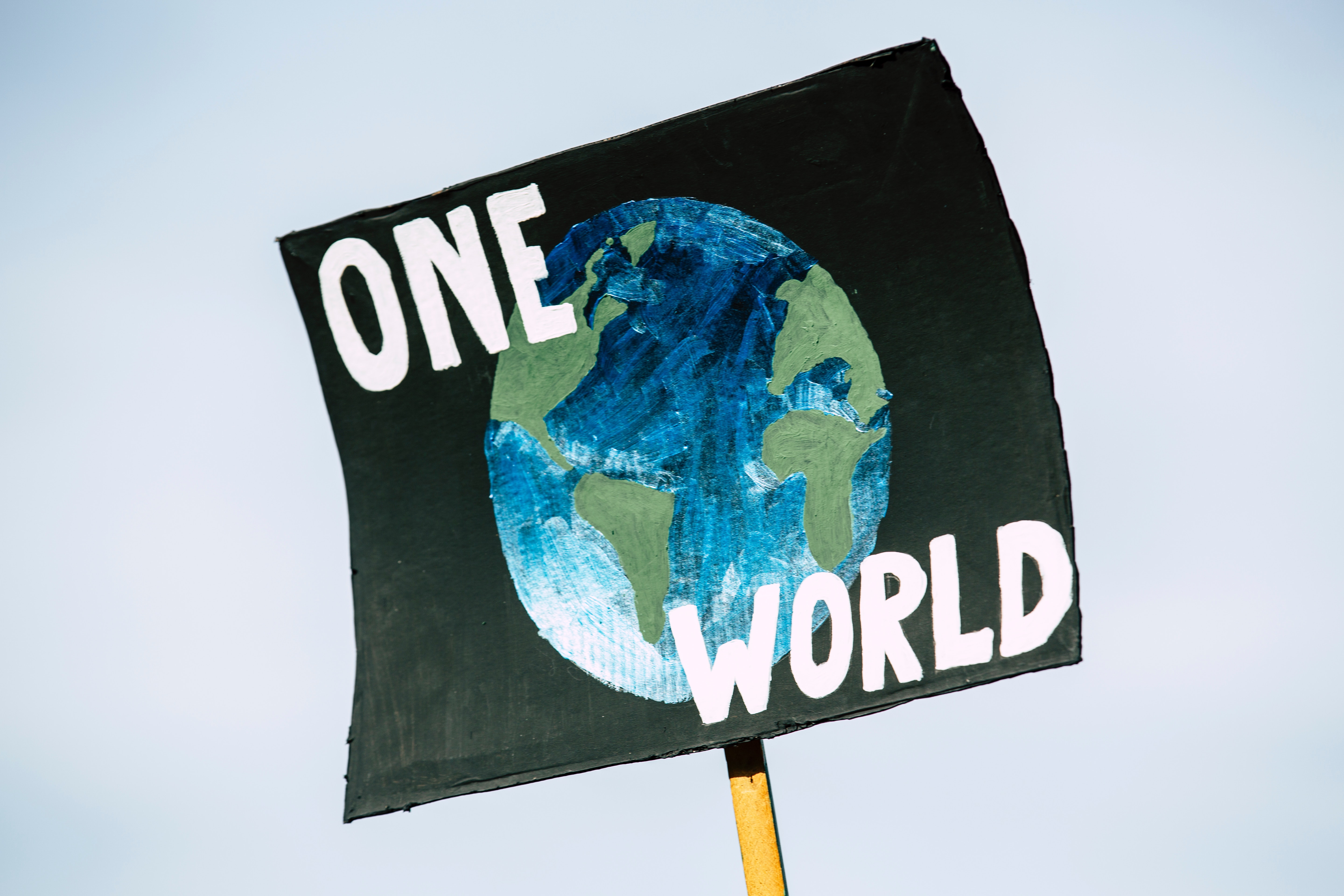 "Sign that says ""One World"" with a picture of Earth."