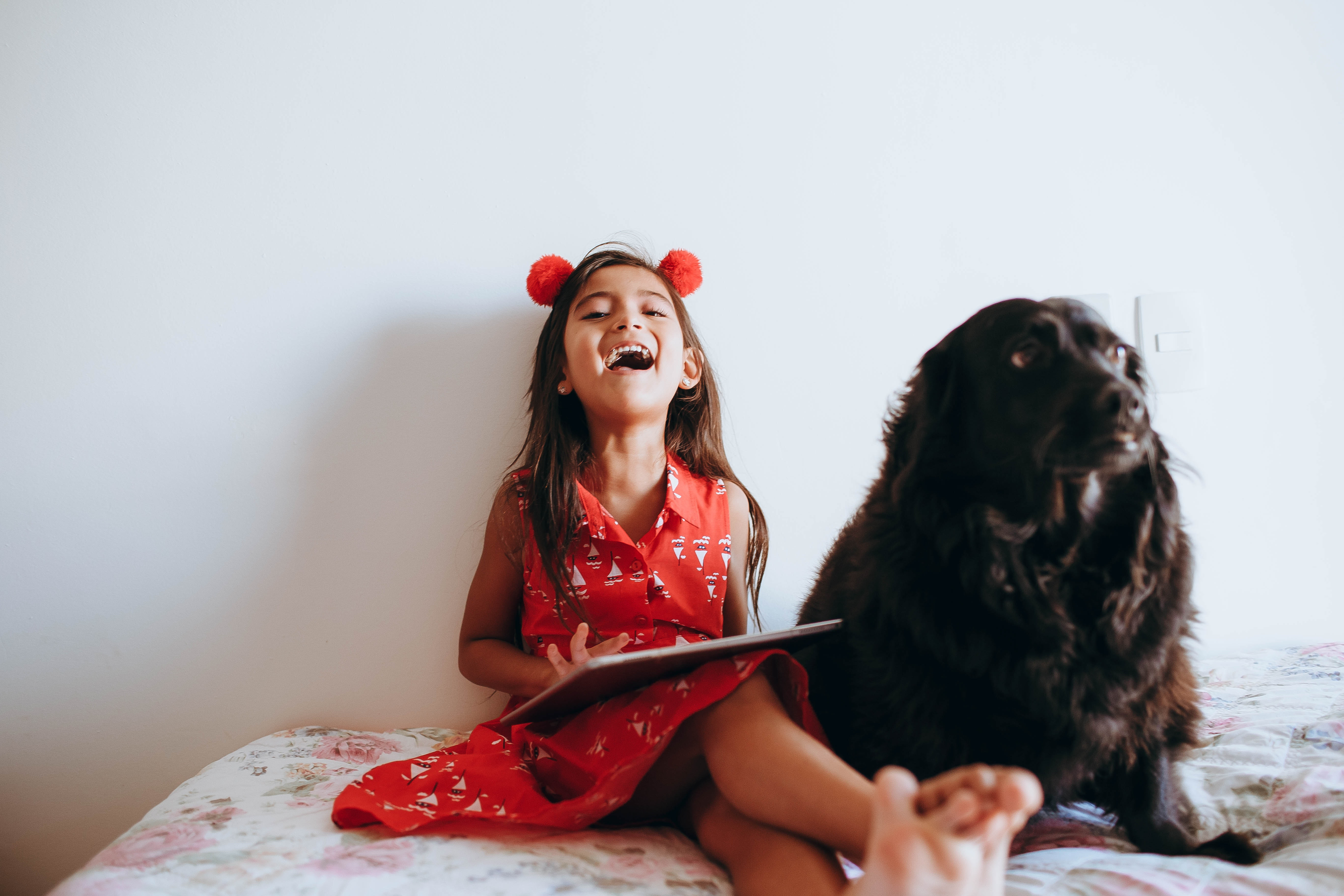 Girl sitting beside black dog on a bed.