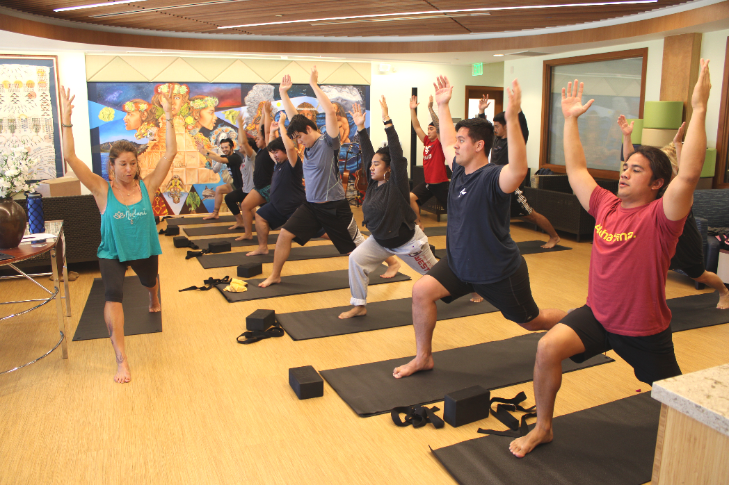 Instructor lead students in yoga session