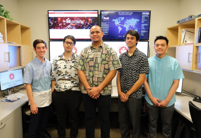 A group of five students standing in front of four wall-mounted monitors at the Cyber Security Coordination Center.
