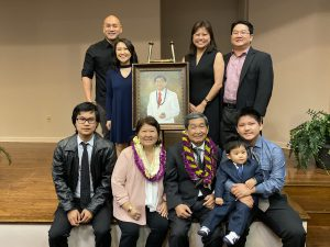 Group photo of Michael Nakasone with his family, all surrounding an easel with a painting of Nakasone.