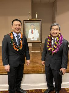 Chadwick Kamei, Michael Nakasone, and between them, an easel with a painting of Nakasone.