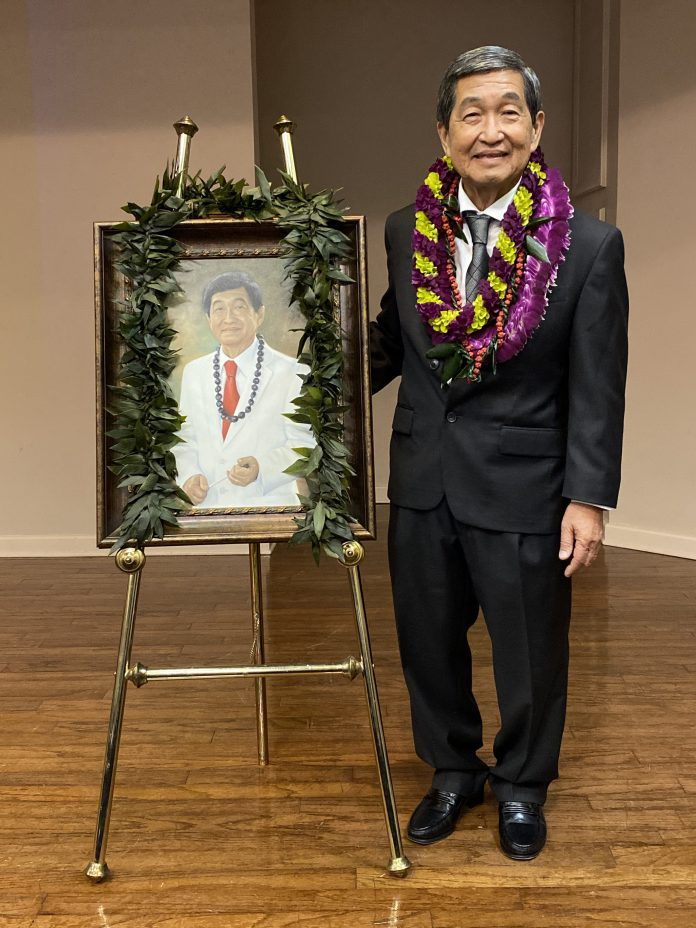 Michael Nakasone standing next to an easel with a painted portrait of himself.
