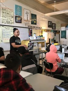 Naturalee ʻIlima Puou standing at the front of a classroom and speaking to students, who are sitting at their desks.