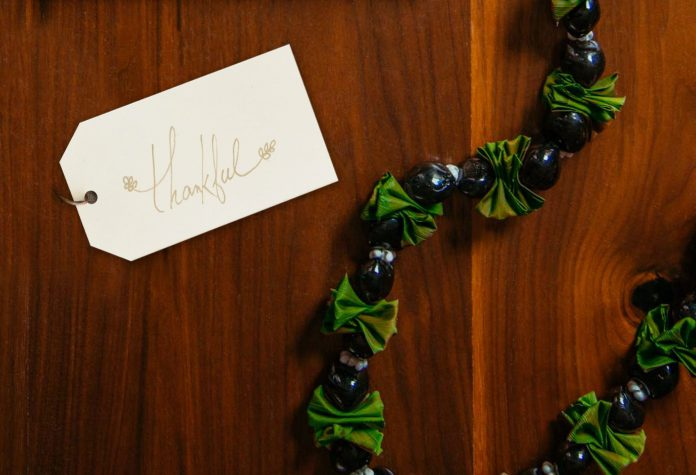 Gift tag with the word thankful written on it and a lei.