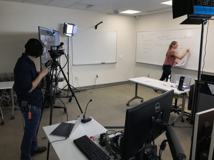 Assistant Professor in Accounting Katie Landgraf writes on a whiteboard during a class while being filmed on camera by Jarrett Lucero, IT Media/Audio Visual Specialist.