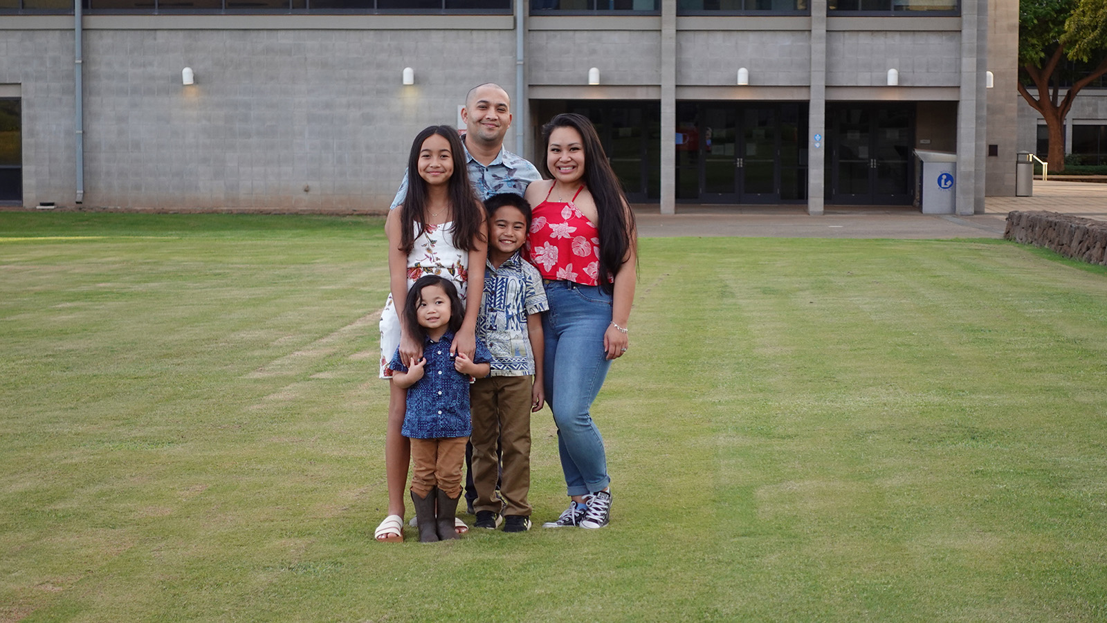 Family posing for a group photo in front of the library at UH West Oʻahu.