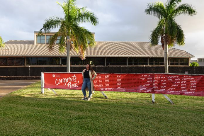 Woman smiling and standing in front of a commencement banner on UH West Oʻahu campus.