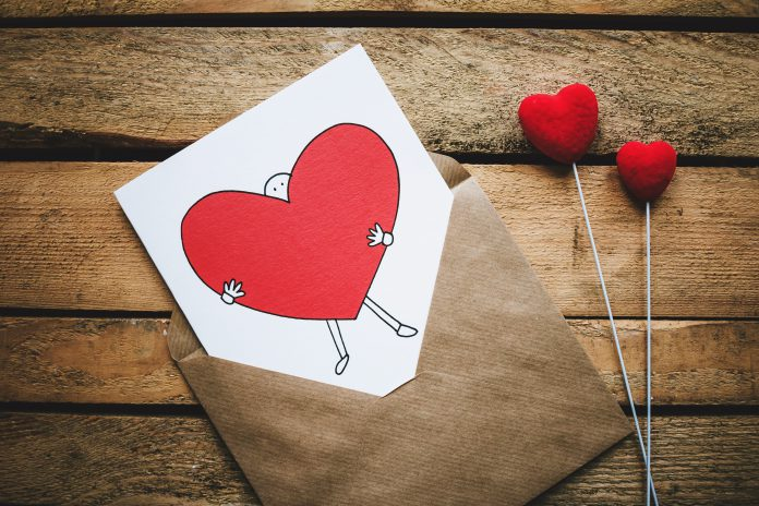Greeting card with a red heart on a wooden table.
