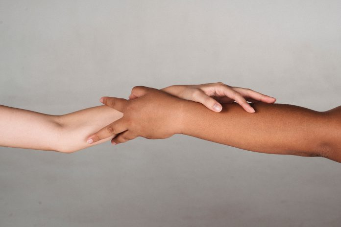 Two arms of different skin colors grabbing hold of each other.