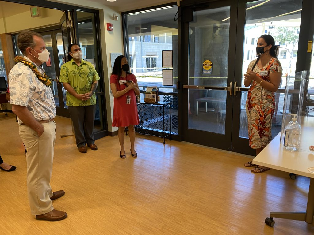 A group stands around in a discussion at the Naʻulu Center.