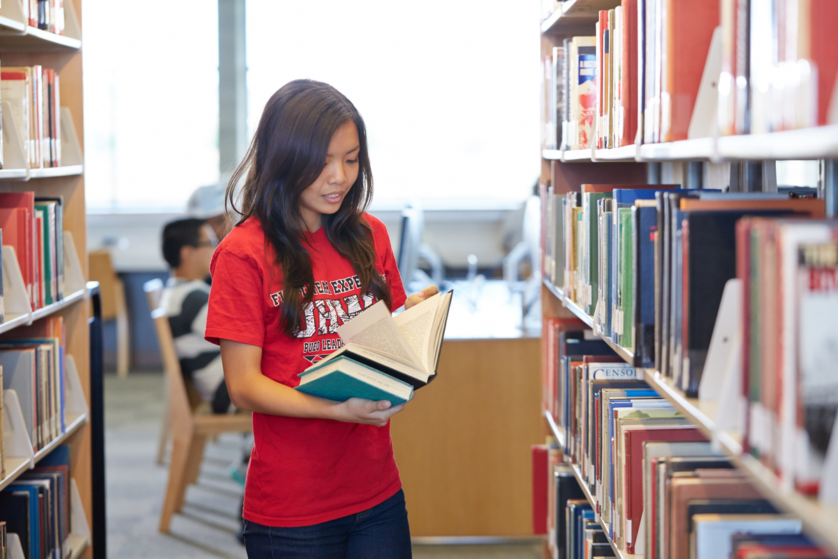 Female student looking at a book in the stacks.
