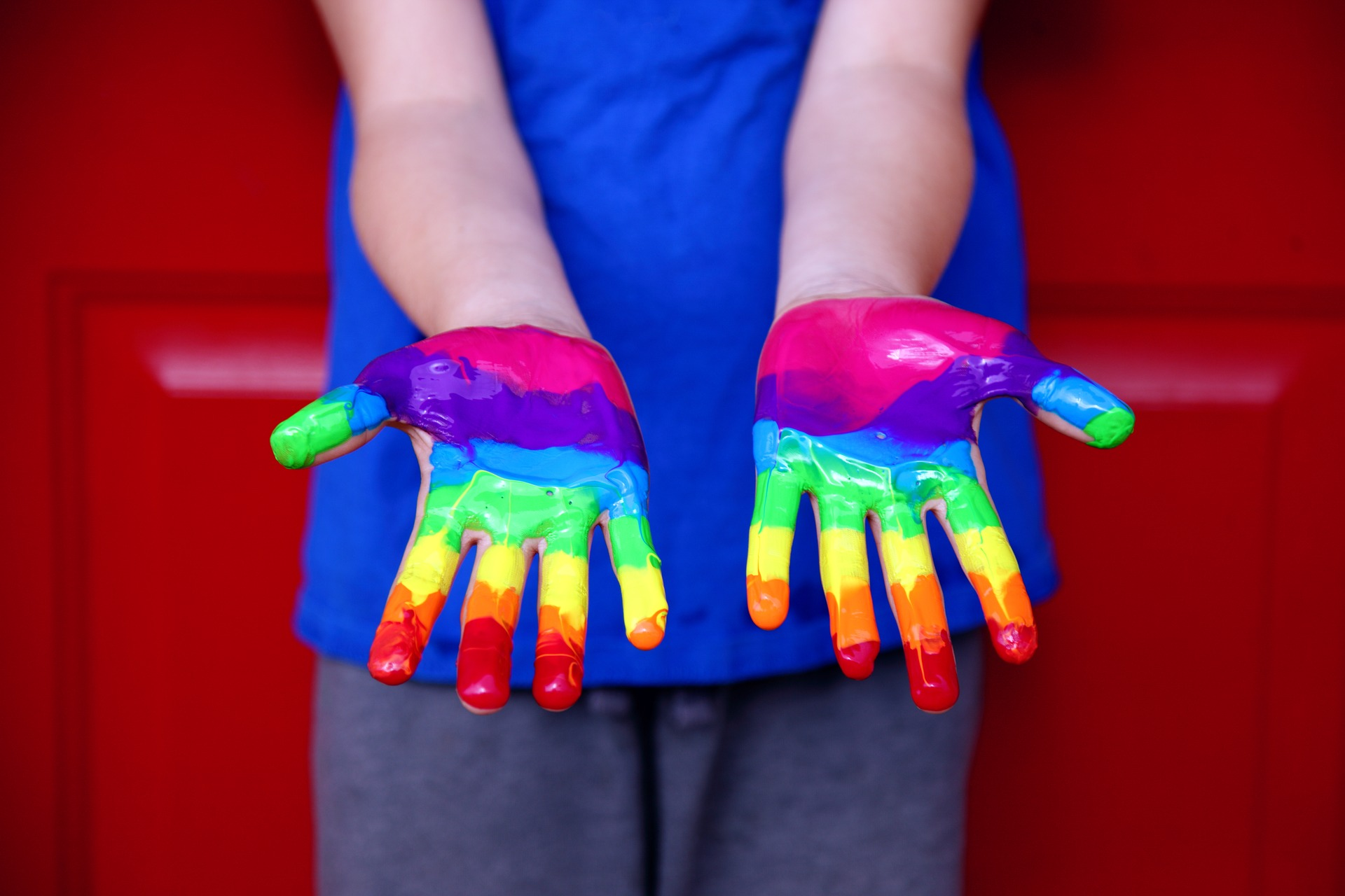 A picture of a pair of hands covered in paint, giving the effect of a rainbow.