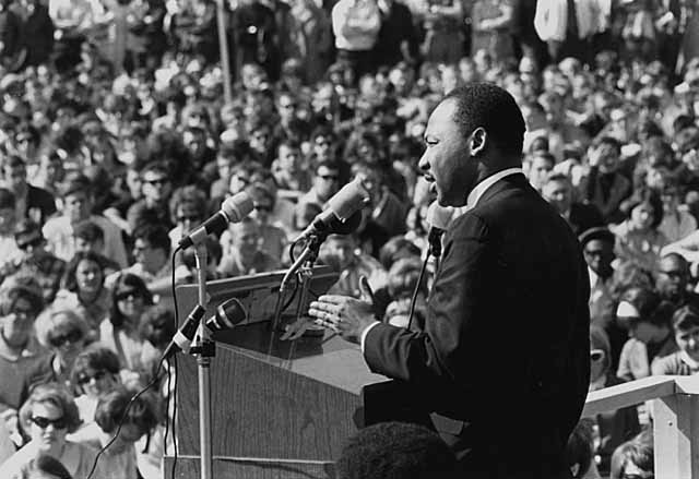 A picture of Martin Luther King giving a speech to a large crowd at St. Paul Campus