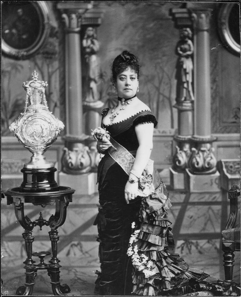 An image of Queen Emma standing in a room with ornate furnishings.