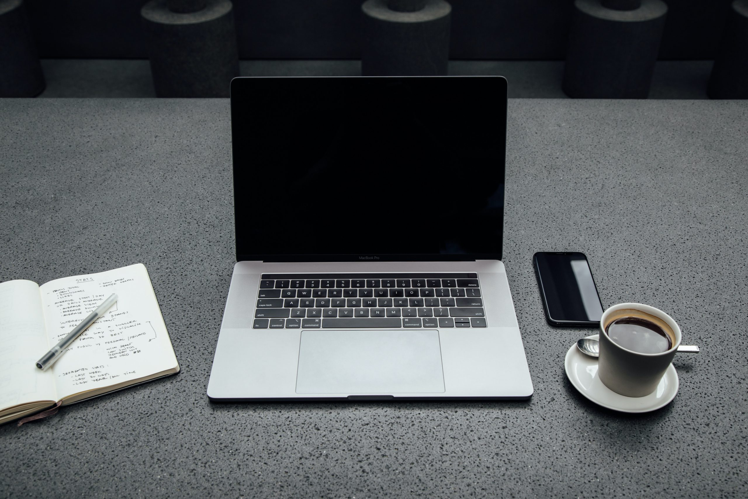 A picture of a workspace that has a laptop, smart phone, notebook, and cup of coffee.