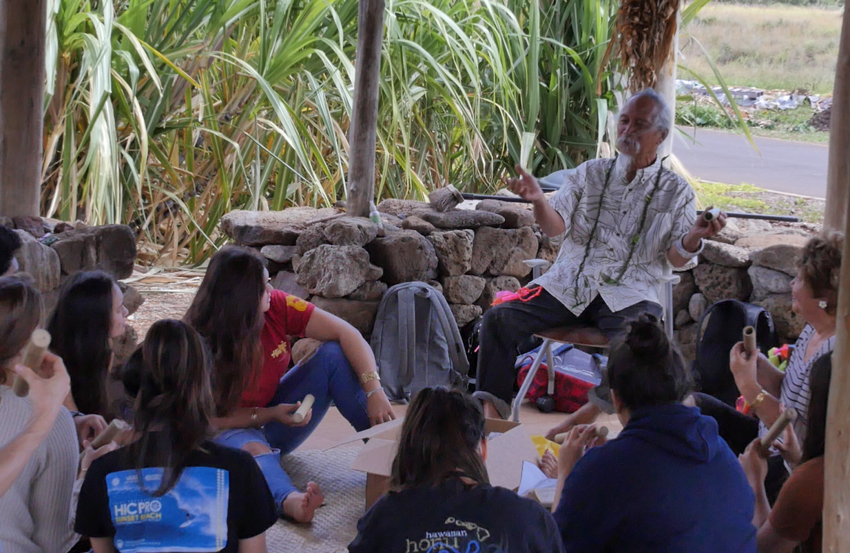 MUS 108 students hosting Uncle Calvin Hoe's ʻohe hano ihu (Hawaiian nose flute) workshop in the student mala (garden).
