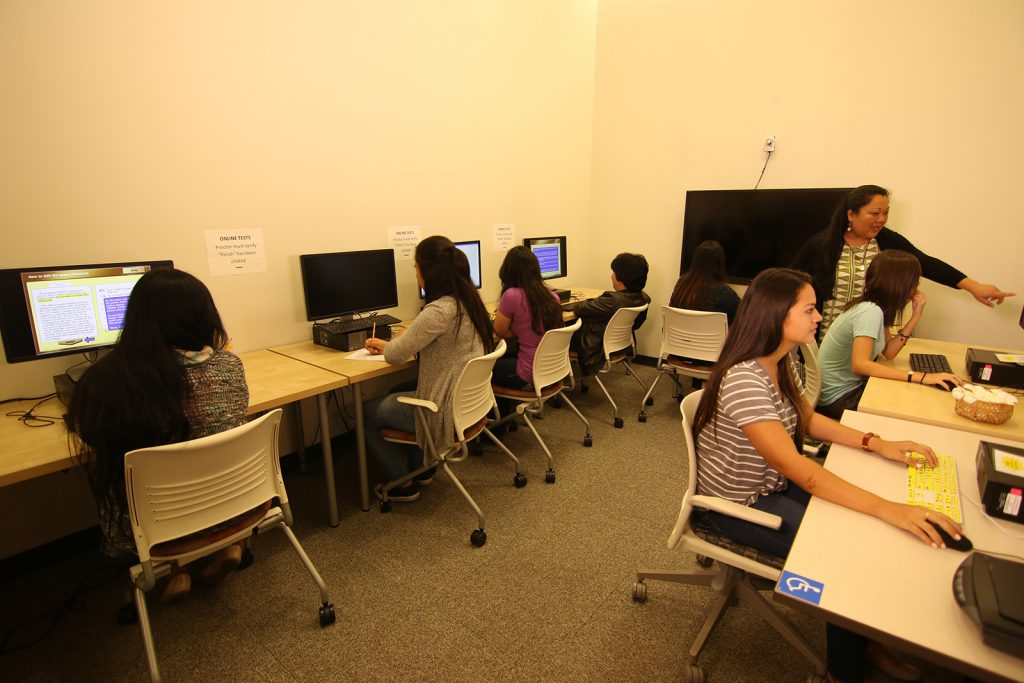 Students completing their exams in the test center with a proctor in the room
