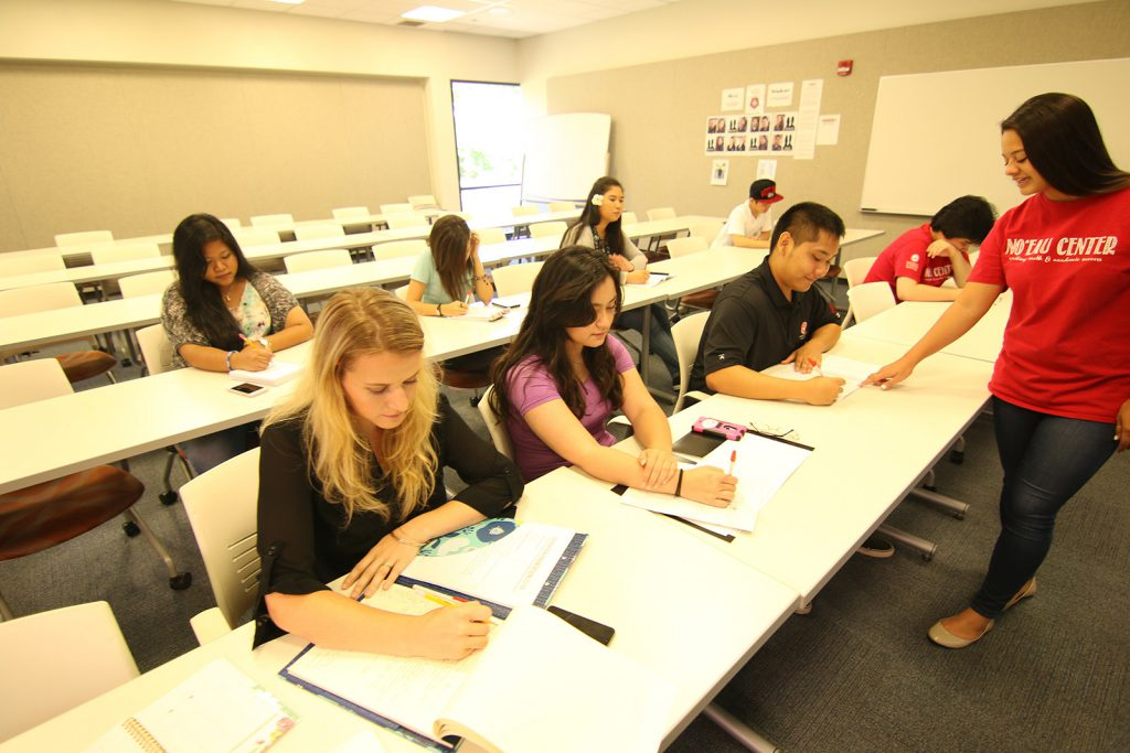 Students working at their desks with a tutor is at the front of the room
