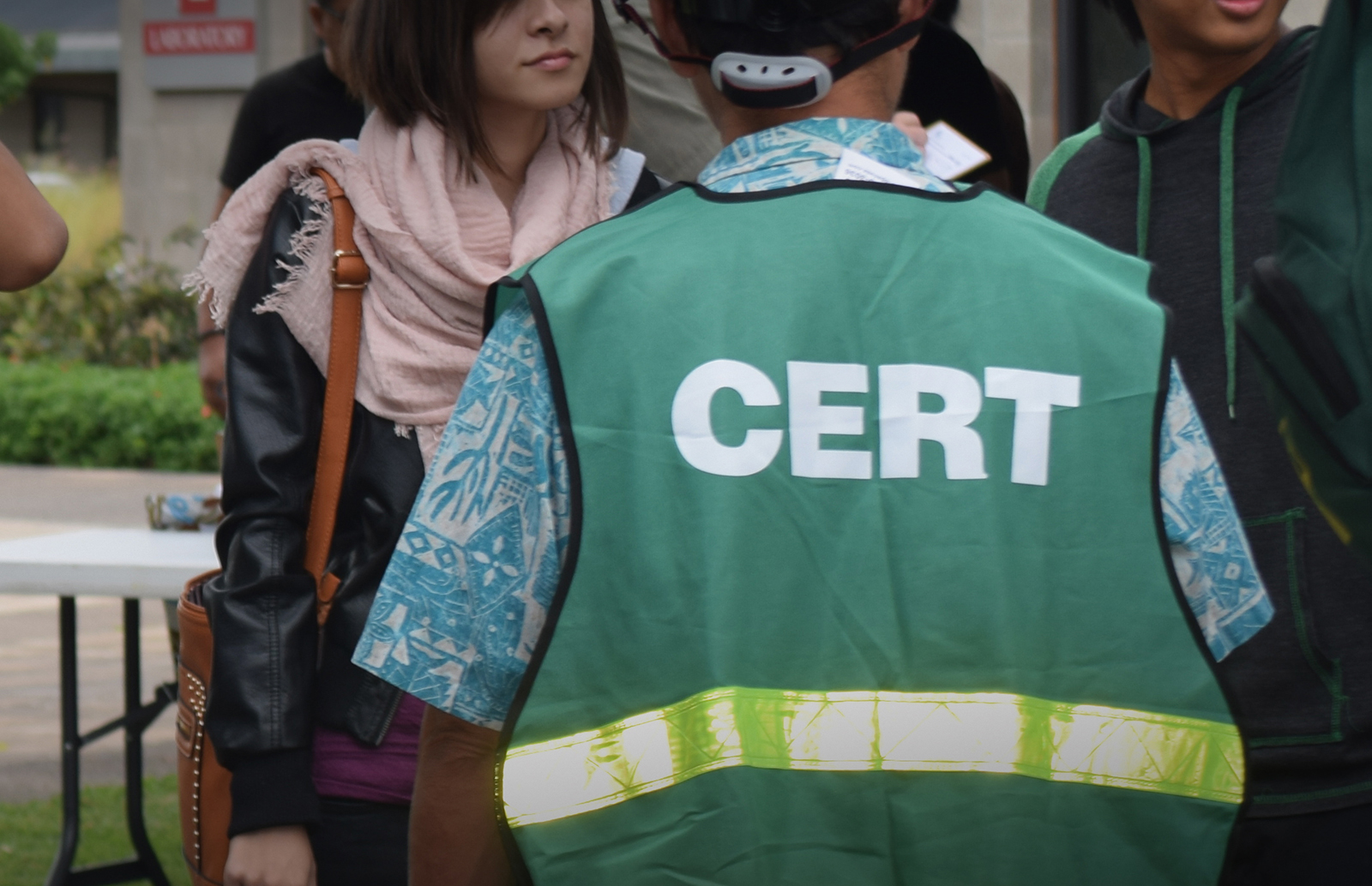 The back of student wearing a Community Emergency Response Team (CERT) green vest.