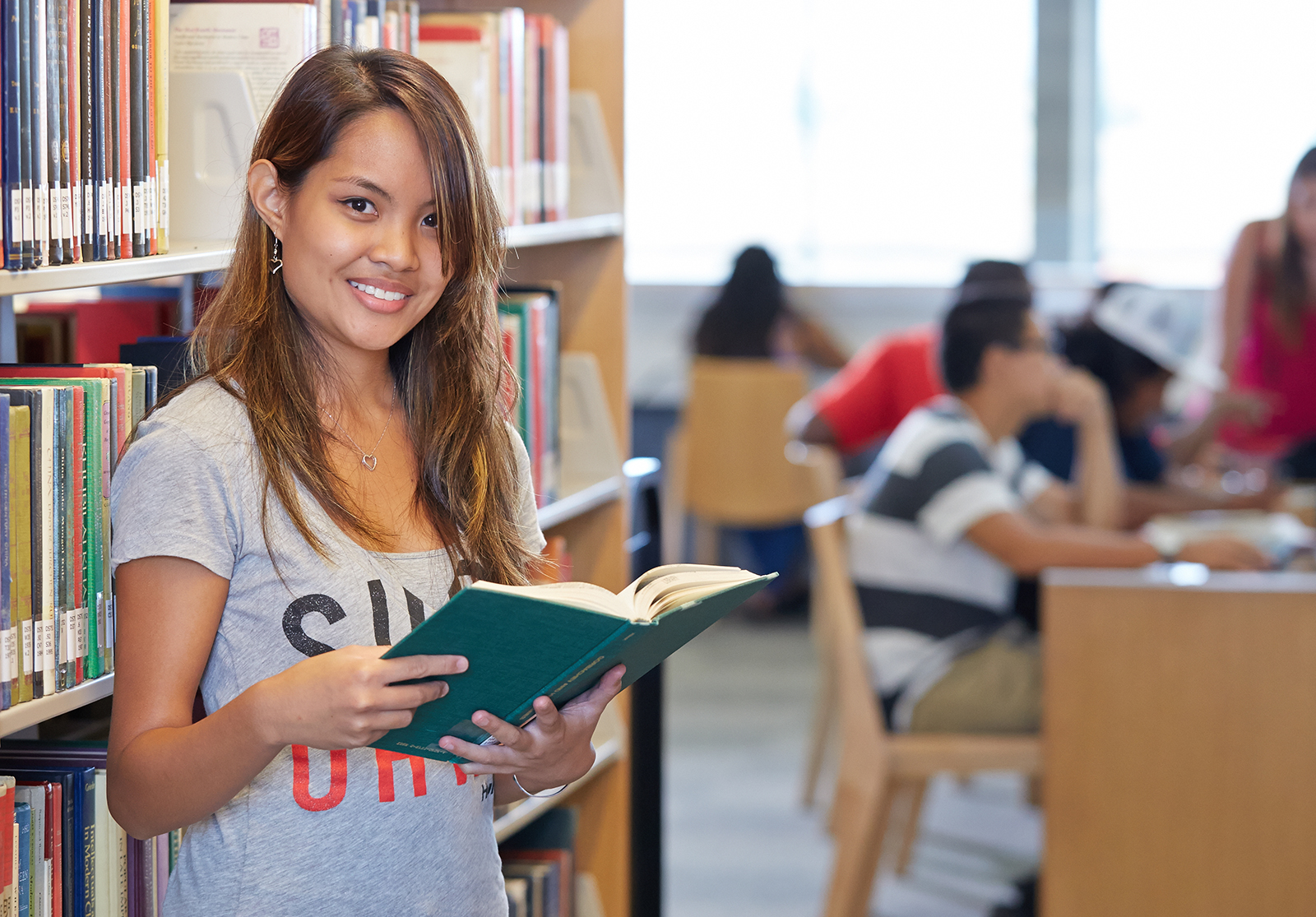 Student smiling while holding a book.