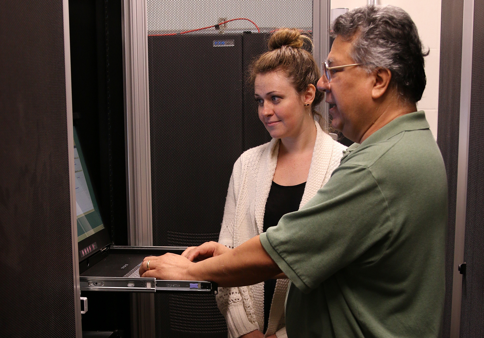 A student and instructor standing at a server keyboard.