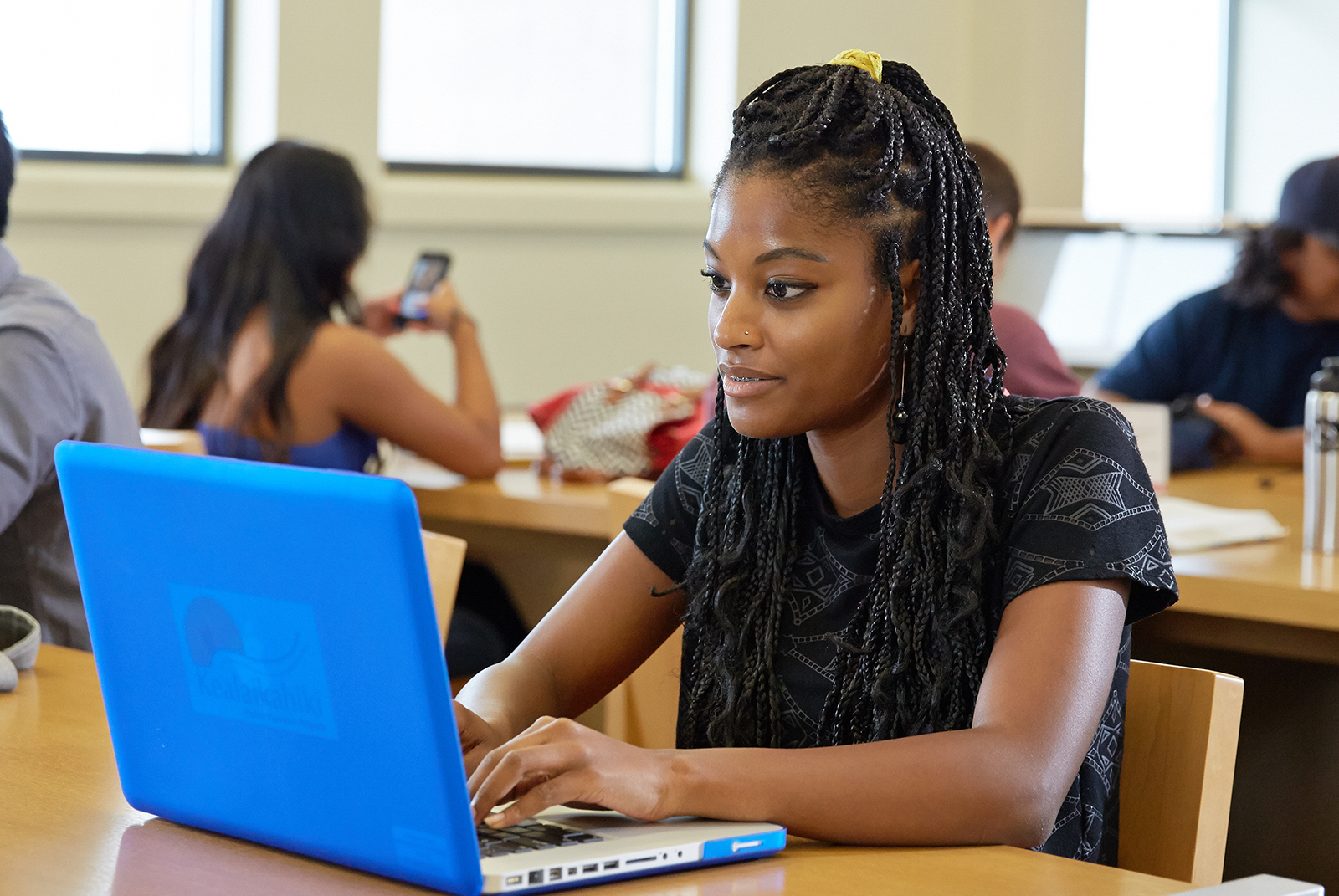 Student sitting in front of a blue laptop.