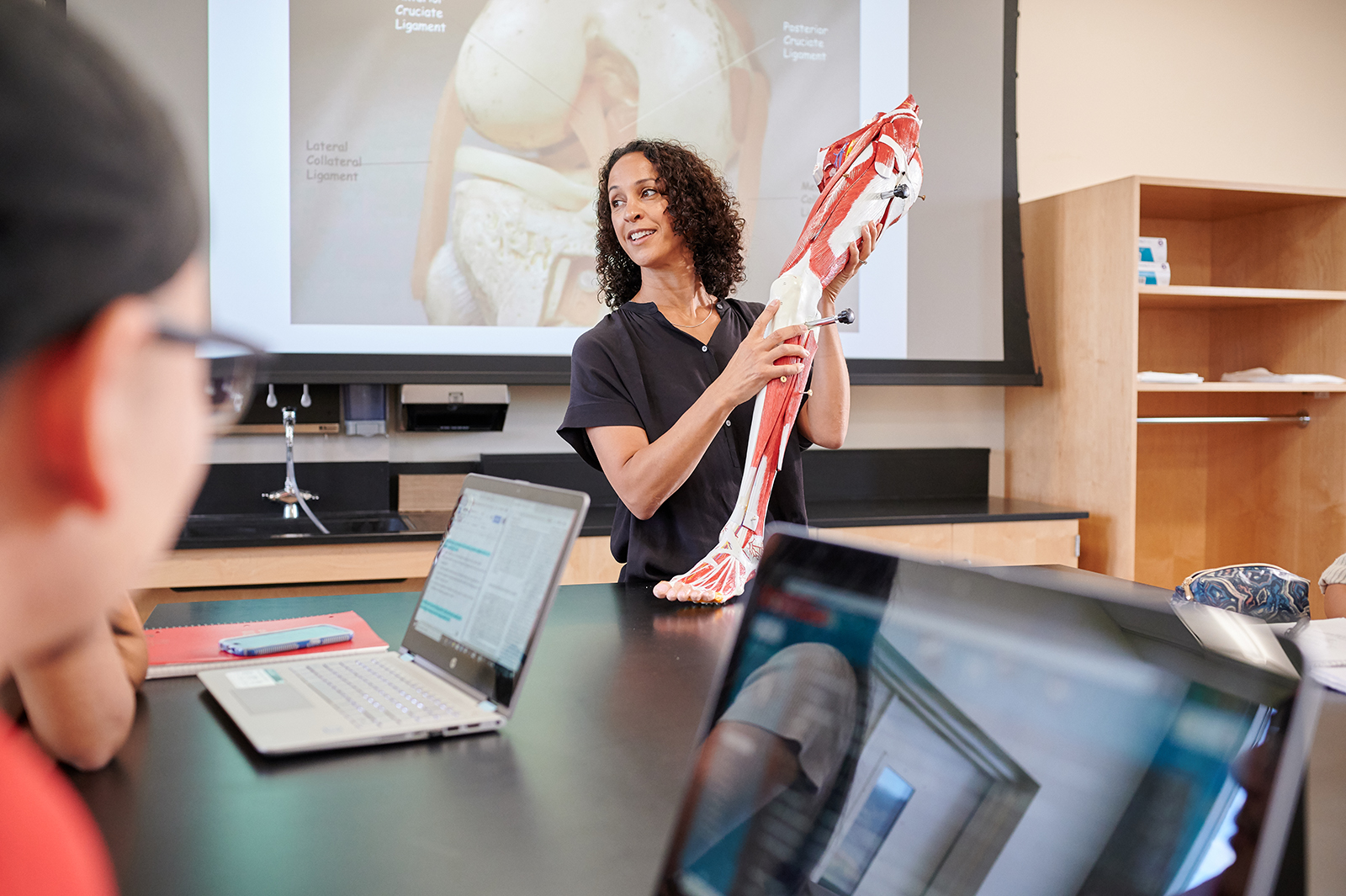 Science professor demonstrating the anatomy of a human leg using a life sized plastic model.