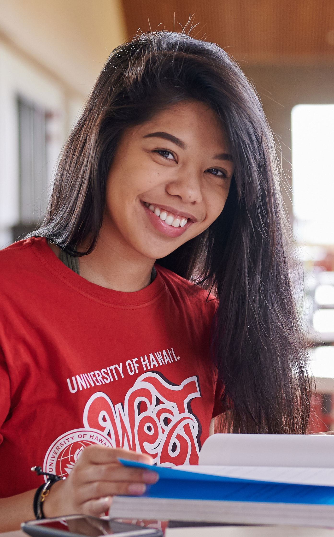 Close-up Of A Student Smiling While Sitting At A Table In The Hallway Wearing A Red T-shirt.